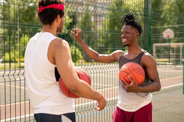 Dois jovens jogadores de basquete multiculturais interagindo após o jogo enquanto estavam perto da cerca Foto Premium