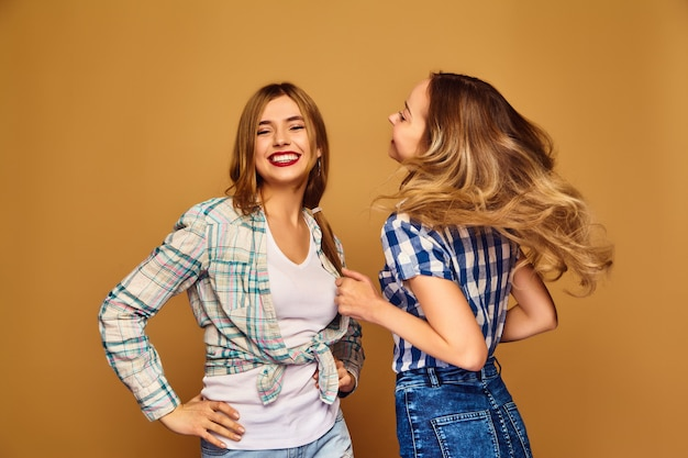 Dois jovens loiro lindo sorrindo em camisas de verão na moda xadrez Foto gratuita