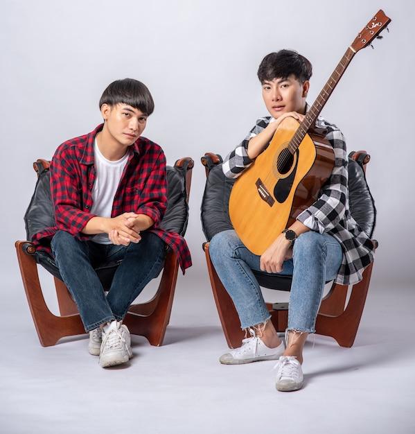 Dois jovens sentados em uma cadeira segurando um violão Foto gratuita