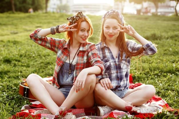 Dois jovens sorrindo hipster garotas se divertindo Foto Premium