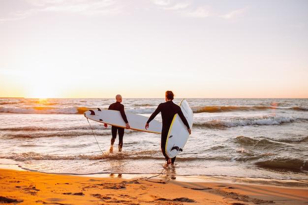 Dois jovens surfistas masculinos em roupas de mergulho pretas com longboards indo para a água no oceano por do sol Foto Premium
