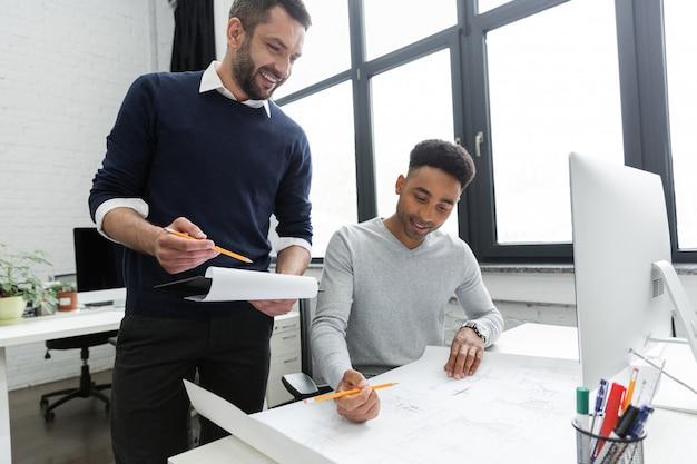 Dois jovens trabalhadores masculinos sorridentes trabalhando em conjunto com documentos Foto gratuita