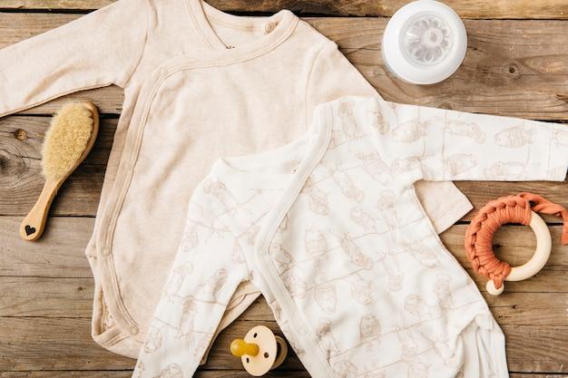 Dois macacão de bebê; escova; garrafa de leite; brinquedo e chupeta na mesa de madeira Foto gratuita