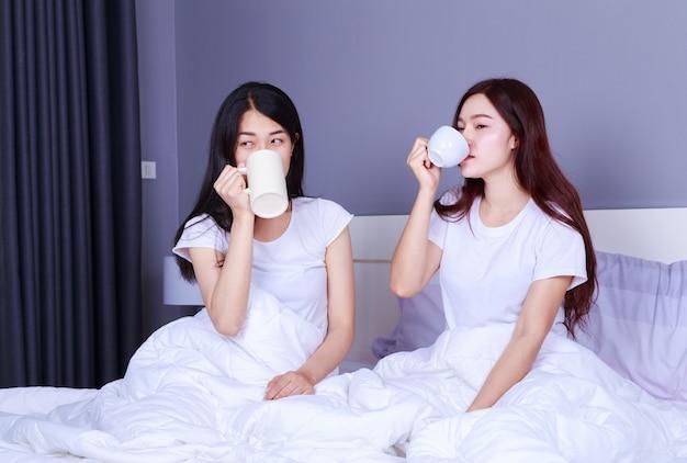 Dois melhores amigos conversando e bebendo uma xícara de café na cama no quarto Foto Premium