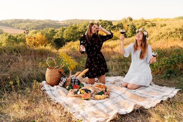Dois melhores amigos no piquenique no campo deitado sobre o sorriso Foto Premium