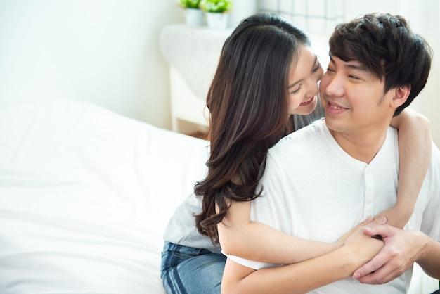 Dois menina asiática nova dos pares rebocam o homem da parte traseira na cama, pessoa romântico de ásia no amor que abraça ao sentar-se na cama, conceito do dia de são valentim com espaço da cópia. Foto Premium