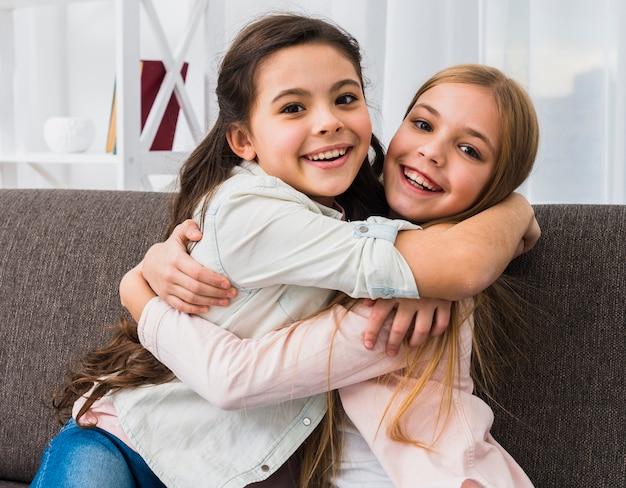 Dois, menina sorridente, abraçar, um ao outro, olhando câmera, casa Foto gratuita