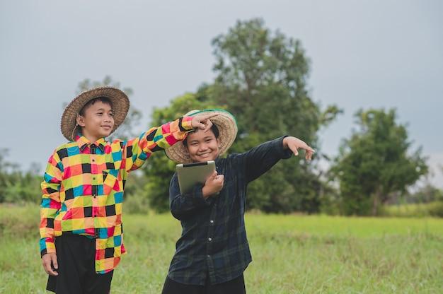 Dois meninos asiáticos usando tablet destacando-se fazendeiro da porta, fazendeiro inteligente de conceito ou escola de estudo de colagem de educação Foto Premium