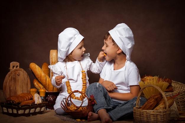 Dois meninos e uma menina estão alimentando uns aos outros biscoitos com prazer posando enquanto estiver jogando chef Foto Premium