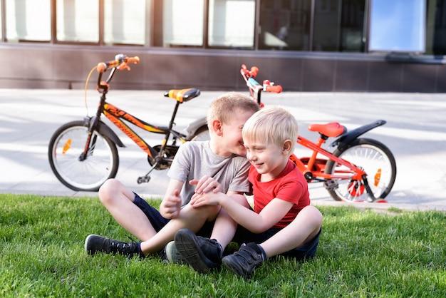 Dois meninos se comunicam sentados na grama. descanse depois de andar de bicicleta, bicicletas ao fundo Foto Premium