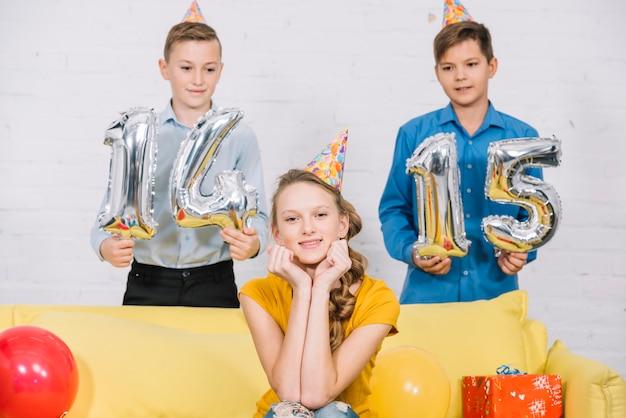 Dois meninos, segurando, numeral, 14, e, 15, foil, balões, em, mão, estar, aniversário, menina Foto gratuita