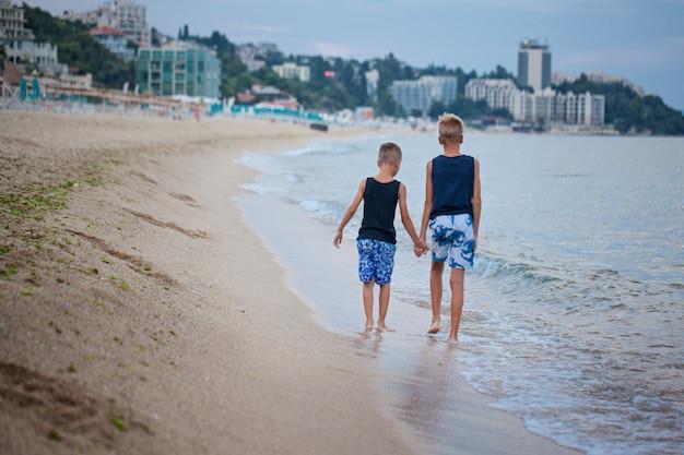 Dois miúdos meninos que andam no verão da praia do mar, melhores amigos felizes que jogam. vista traseira Foto Premium