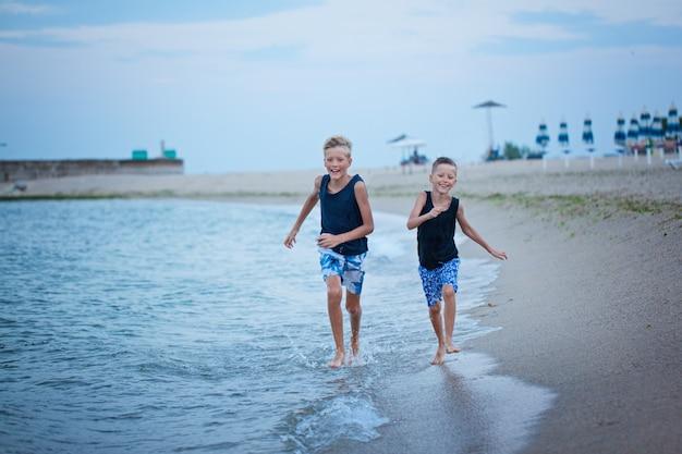 Dois miúdos meninos que andam no verão da praia do mar, melhores amigos felizes que jogam. Foto Premium