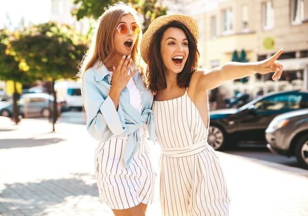 Dois moda morena hippie elegante jovem e modelos de mulheres loiras em dia ensolarado de verão em roupas hipster posando no fundo da rua. apontando as vendas da loja Foto gratuita