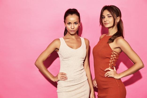 Dois modelos de mulheres bonitas e sorridentes usam vestido de algodão com roupas de tendência de design elegante, estilo casual de verão para data da festa a pé. mulheres quentes morena empresária posando na parede rosa Foto gratuita