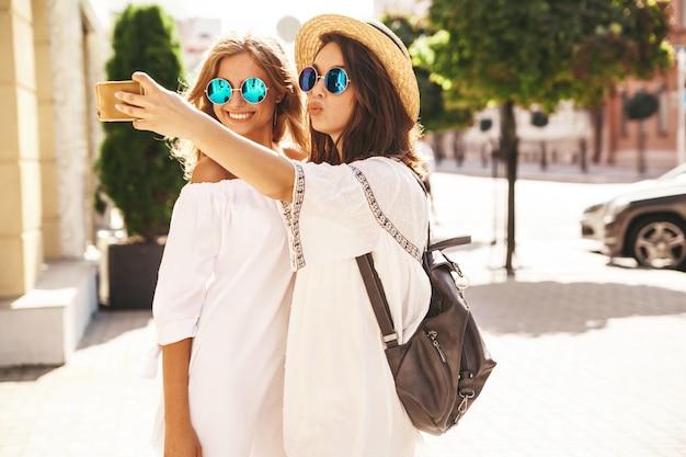 Dois modelos de mulheres jovens loiras e loiras de hippie sorrindo em dia ensolarado de verão em roupas brancas hipster tirando fotos de selfie para mídias sociais no telefone. Foto gratuita