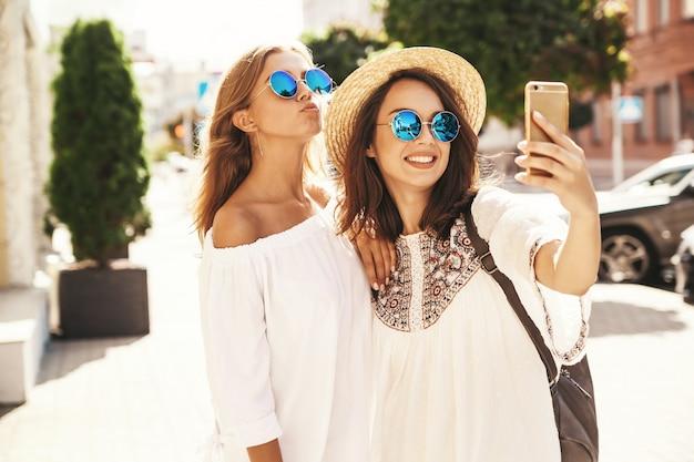 Dois modelos de mulheres jovens loiras e morenas de hippie sorrindo loira no verão hipster branco vestem tirar fotos de selfie para mídias sociais no telefone. cara de surpresa, emoções, Foto gratuita
