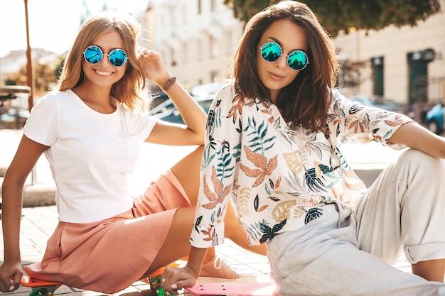 Dois modelos em dia de sol de verão em roupas hipster, sentado no skate centavo na rua Foto gratuita