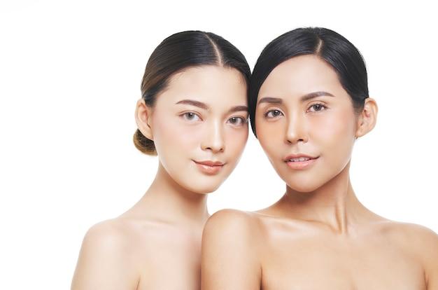 Dois modelos femininos com aparência natural, mulher asiática, tratamento facial, cosmetologia, tratamento de beleza Foto Premium