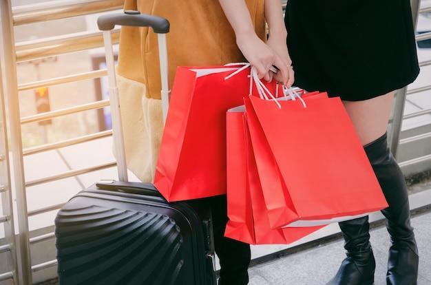 Dois, mulher jovem, segurando, muitos, coloridos, sacolas vermelhas, e, bagagem, andar, junto Foto Premium