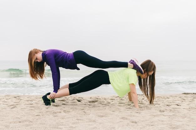 Dois, mulheres jovens, em, esportes, roupa, fazendo, um, ginástico, exercício, praia Foto Premium