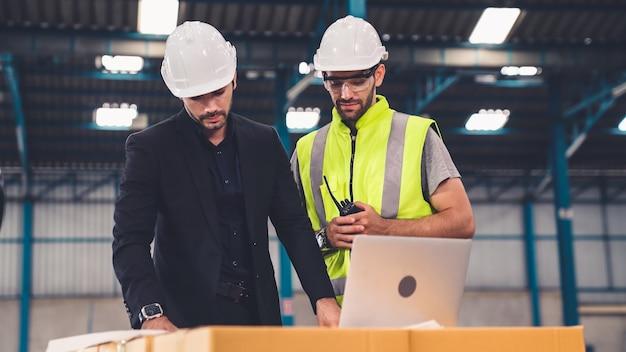 Dois operários trabalhando e discutindo o plano de manufatura na fábrica Foto Premium