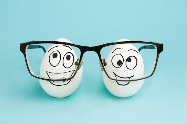 Dois ovos engraçados olham através de lentes de óculos. correção da visão Foto Premium