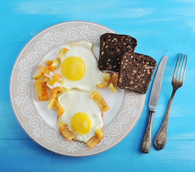 Dois ovos fritos com pimenta e duas fatias de pão de centeio em um prato, faca e garfo em uma superfície de madeira azul Foto Premium