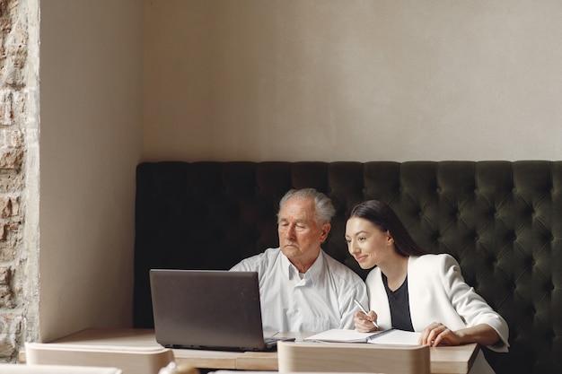 Dois parceiros de negócios, trabalhando com um laptop em um café Foto gratuita