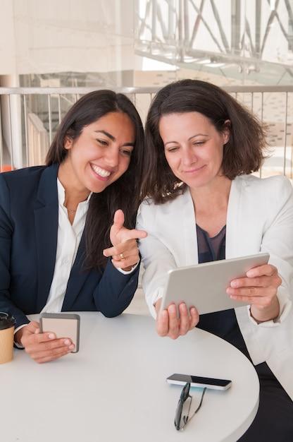 Dois parceiros femininos sorridentes usando gadgets no café moderno Foto gratuita