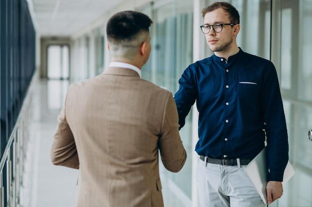 Dois parceiros masculinos, apertando as mãos no escritório Foto gratuita