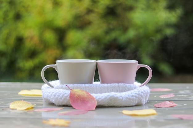 Dois, pastel, copos, com, chá quente, em, branca, tricotado, echarpe, ligado, tabela molhada Foto Premium