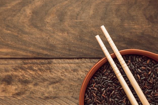 Dois, pauzinhos, sobre, a, arroz preto, grão, tigela, ligado, madeira, fundo Foto gratuita