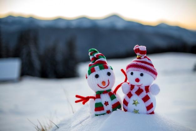 Dois pequenos brinquedos engraçados bebê boneco de neve em chapéus de malha e lenços na neve profunda ao ar livre Foto Premium