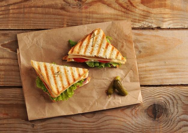 Dois picles de sanduíche em uma toalha de papel na superfície de madeira Foto Premium