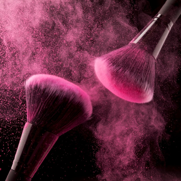 Dois pincéis cosméticos e pó-de-rosa sobre fundo escuro Foto gratuita
