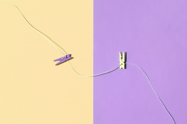 Dois pinos de madeira coloridos e pequena corda mentem sobre fundo de textura de cores pastel de amarelo e violeta de moda Foto Premium