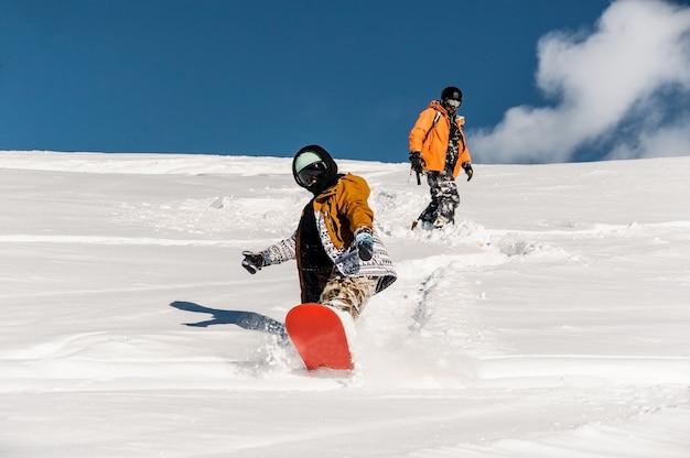 Dois praticantes de snowboard no sportswear descendo a encosta da montanha Foto Premium
