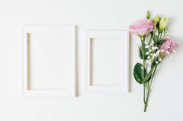 Dois quadros vazios de madeira perto do eustoma rosa e flores da respiração do bebê no fundo branco Foto gratuita