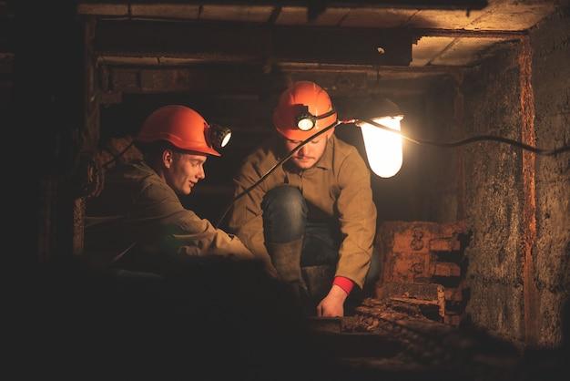 Dois rapazes de uniforme de trabalho e capacetes de proteção, sentados em um túnel baixo. trabalhadores da mina Foto Premium