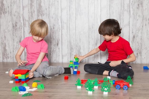 Dois rapazes giros em camisetas rosa e vermelhas brincando com brinquedos Foto gratuita