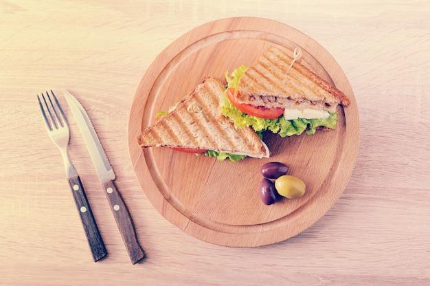 Dois sanduíches triangulares e azeitonas em uma placa redonda de madeira Foto Premium