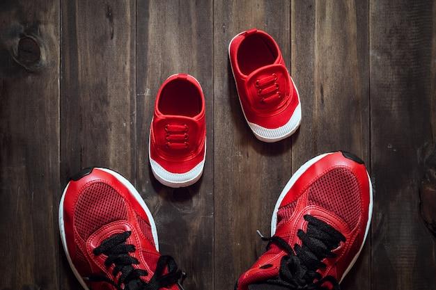 Dois sapatos de desporto vermelho ou tênis de mãe ou pai e filho em fundo de madeira Foto Premium