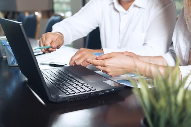Dois sócios comerciais que sentam-se em uma tabela junto e que trabalham. Foto Premium