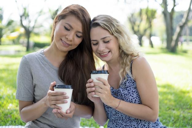 Dois, sorrindo, bonito, mulheres, segurando, plástico, copos café, em, parque Foto gratuita