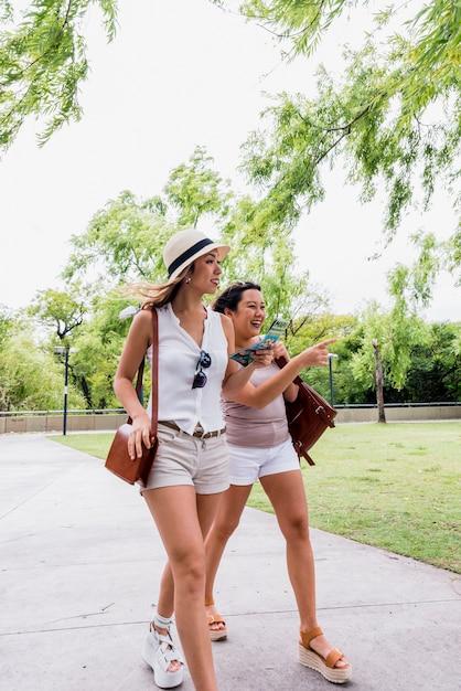 Dois, sorrindo, elegante, mulheres jovens, andar, junto, parque Foto gratuita