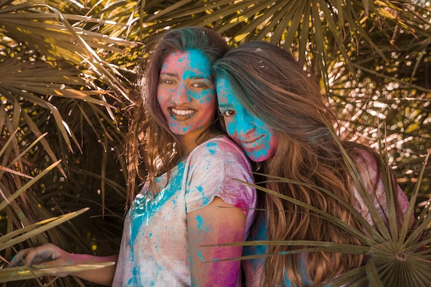 Dois, sorrindo, mulheres jovens, com, holi, cor, ligado, dela, rosto, olhando câmera Foto gratuita