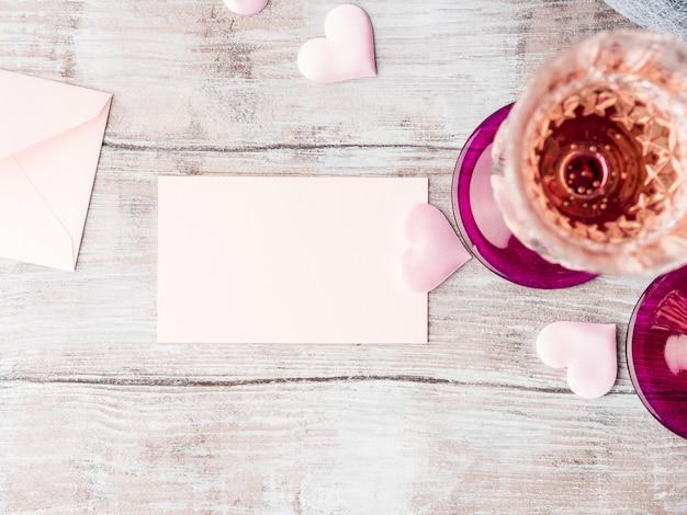 Dois stemmed vidros do champanhe com o cartão de nota cor-de-rosa do papel vazio dos corações para encher-se com seu texto no fundo textured de madeira. Foto Premium