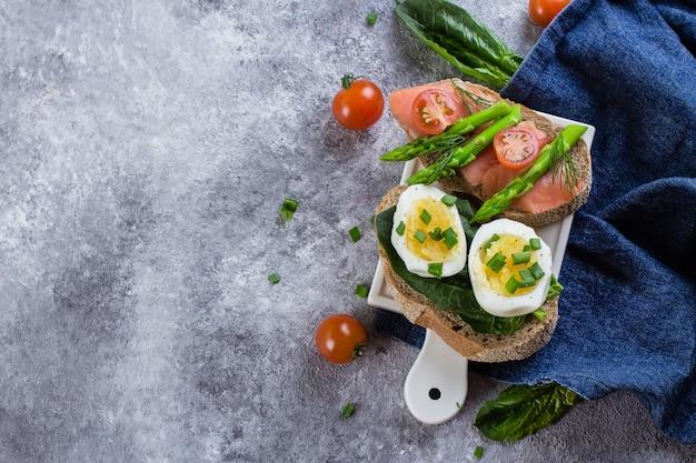 Dois tipos de sanduíche com espinafre, ovos cozidos e salmão salmão, tomate cereja, espargos verdes Foto Premium