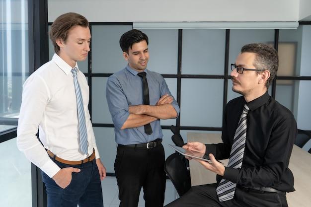 Dois trabalhadores de escritório incertos que relatam ao chefe. Foto gratuita